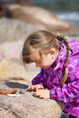 Girl Examining Beach Pebble — Stock Photo
