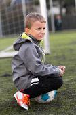 少年サッカー ボールの上に座って — ストック写真