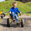 Caucasian boy having fun in moon buggy — Stock Photo