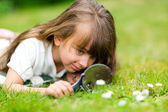 Young girl with magnifier — Stock Photo