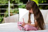 年轻的女孩写在记事本 — 图库照片