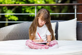 Girl sitting on patio with notepad — Stock Photo