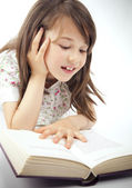 Sweet happy little girl reading a book — Stock Photo