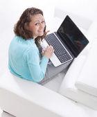 Glad ung kvinna sitter på soffan med en bärbar dator — Stockfoto