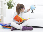 Young girl studying geography with an earth globe — Stock Photo