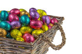 Colorful chocolate easter eggs in a basket — Stock Photo