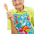 Happy old woman with wooden spoon — Stock Photo