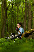 Girl with her bike in the forest — Stock Photo
