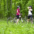 Girls biking in the forest — Stock Photo #27361441