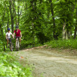 Girls biking in the forest — Stock Photo #27361495