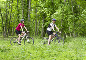 Girls biking in the forest — Stock Photo