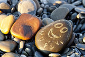 Stone with a painted face — Stock Photo
