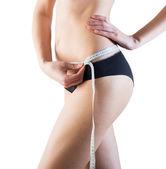 Sporty woman with slim body measuring waistline — Stock Photo