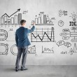Businessman drawing  business plan, graph, chart on wall — Stock Photo #47875003