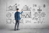 Businessman drawing  business plan, graph, chart on wall — Stock Photo