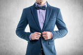 Handsome elegant young fashion man in coat tuxedo classical costume suit and bow tie — Stock Photo