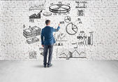 Businessman drawing  business plan, graph, chart on wall — Stok fotoğraf
