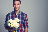 Young beautiful headsome attractive enamored man casual stule with flowers — Stock Photo
