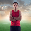 Athletic man, sportsman on background green football soccer field with the blue sky sunset — Stock Photo #48237455