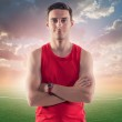 Athletic man, sportsman on background green football soccer field with the blue sky sunset — Stock Photo #48264015