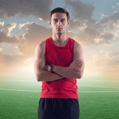 Athletic man, sportsman on background green football soccer field with the blue sky sunset — Stock Photo