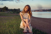 Young beauty smiling relaxing girl woman sitting near river or lake in nature outdoors portrait. Soft sunny colors. Sunset sunbeams. — Stock Photo