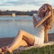 Sunny outdoors portrait of charming romantic girl with long hair under sunset. Summer evening Attractive young woman sitting on the beach near a river. Photo toned style Instagram filters — Stock Photo #48786815