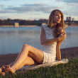 Sunny outdoors portrait of charming romantic girl with long hair under sunset. Summer evening Attractive young woman sitting on the beach near a river. Photo toned style Instagram filters — Stock Photo #48786823