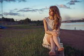 Young beauty smiling relaxing girl woman sitting near river or lake in nature outdoors portrait. Soft sunny warm colors. Sunset sunbeams. Photo toned style Instagram filters — Stock Photo