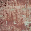 Rough textured background red old cement wall with stains, dry cracked peeling faded paint — Stock Photo #49438915