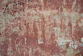Rough textured background red old cement wall with stains, dry cracked peeling faded paint — Stock Photo