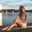 Sunny outdoors portrait of charming romantic girl with long hair under sunset. Summer evening Attractive young woman sitting on the beach near a river. Photo toned style Instagram filters — Stock Photo #49442713