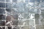 Stone into squares same sort as background. — Stock Photo
