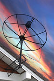 Satellite dish Stuck to roof of house on Evening light. — Stock Photo