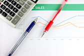 Pen and Calculator resting on Statistical graphs. — Stock Photo