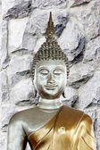 Buddha statue in the background of stone wall. — Stock Photo