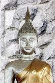 Posąg buddy w tle kamiennego muru. — Zdjęcie stockowe