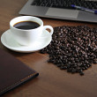 Stock Photo: Coffee in white cup nearby computer notebook.