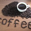 White coffee cup resting on coffee beans and text Coffee on wood — Stock Photo