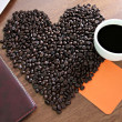 Coffee beans arranged a heart shape and placed paper Notebook wi — Stock Photo