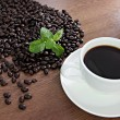 Coffee beans and green peppermint near a white coffee cup. — Stock Photo #32547439