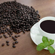 Coffee beans and green peppermint near a white coffee cup. — Stock Photo #32547539