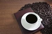 Taza de café con leche y libro sobre la madera vieja mesa cerca del café — Foto de Stock
