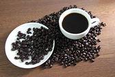 Xícara de café branco descansando em grãos de café. — Fotografia Stock