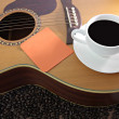 White coffee cup and Notebook paper orange resting on guitar. — Stock Photo