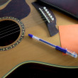 Notebook orange paper and pen on the guitar. — Stock Photo #32553745