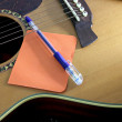 Notebook orange paper and pen on the guitar. — Stock Photo #32553987