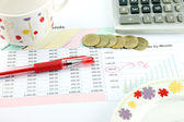 The Red Pen,cup,Calculator and money Coins on Business graph. — Stock Photo
