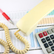 Telephone and calculator placed on Business graph. — Stock Photo #32601149