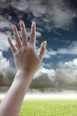Hand can be seen in the five inches on gark sky Background. — Stock Photo